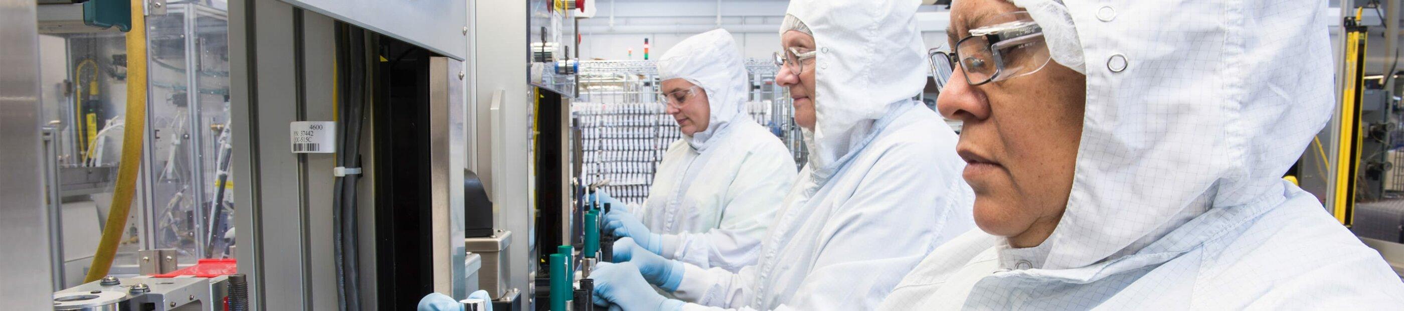 women in white hazmat suit working on machines