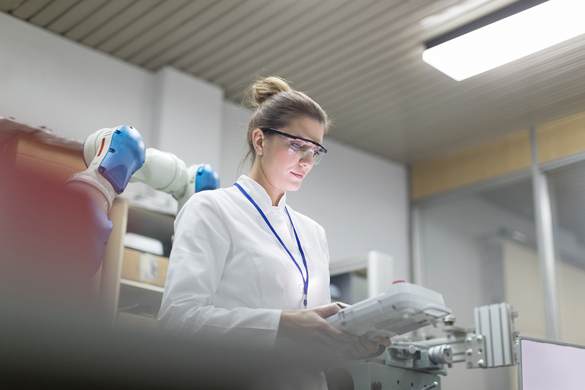 woman in lab coat with goggles looking at clipboard
