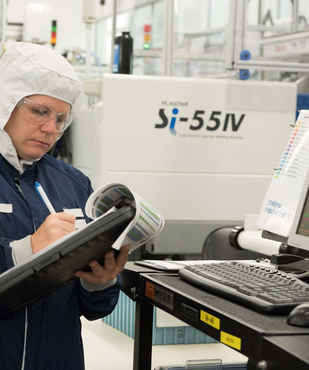 woman taking notes on clipbard in manufacturing facility
