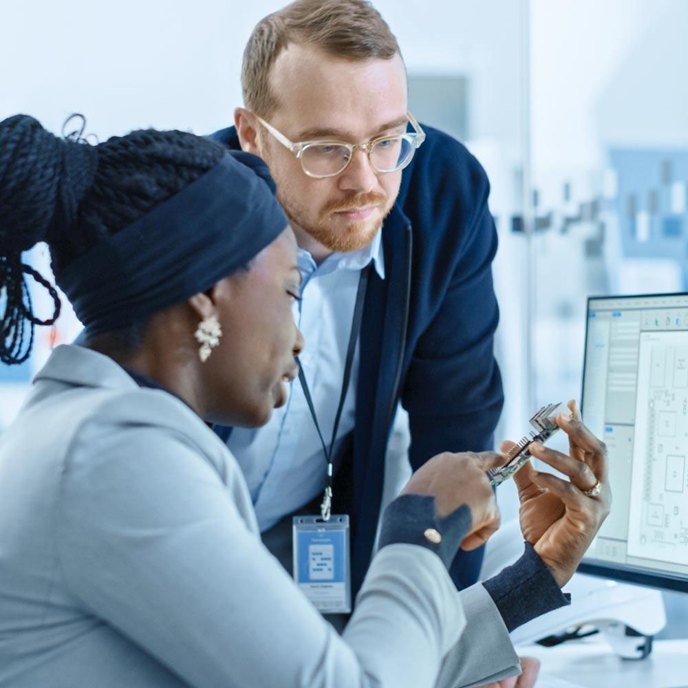 man and woman looking at computer part