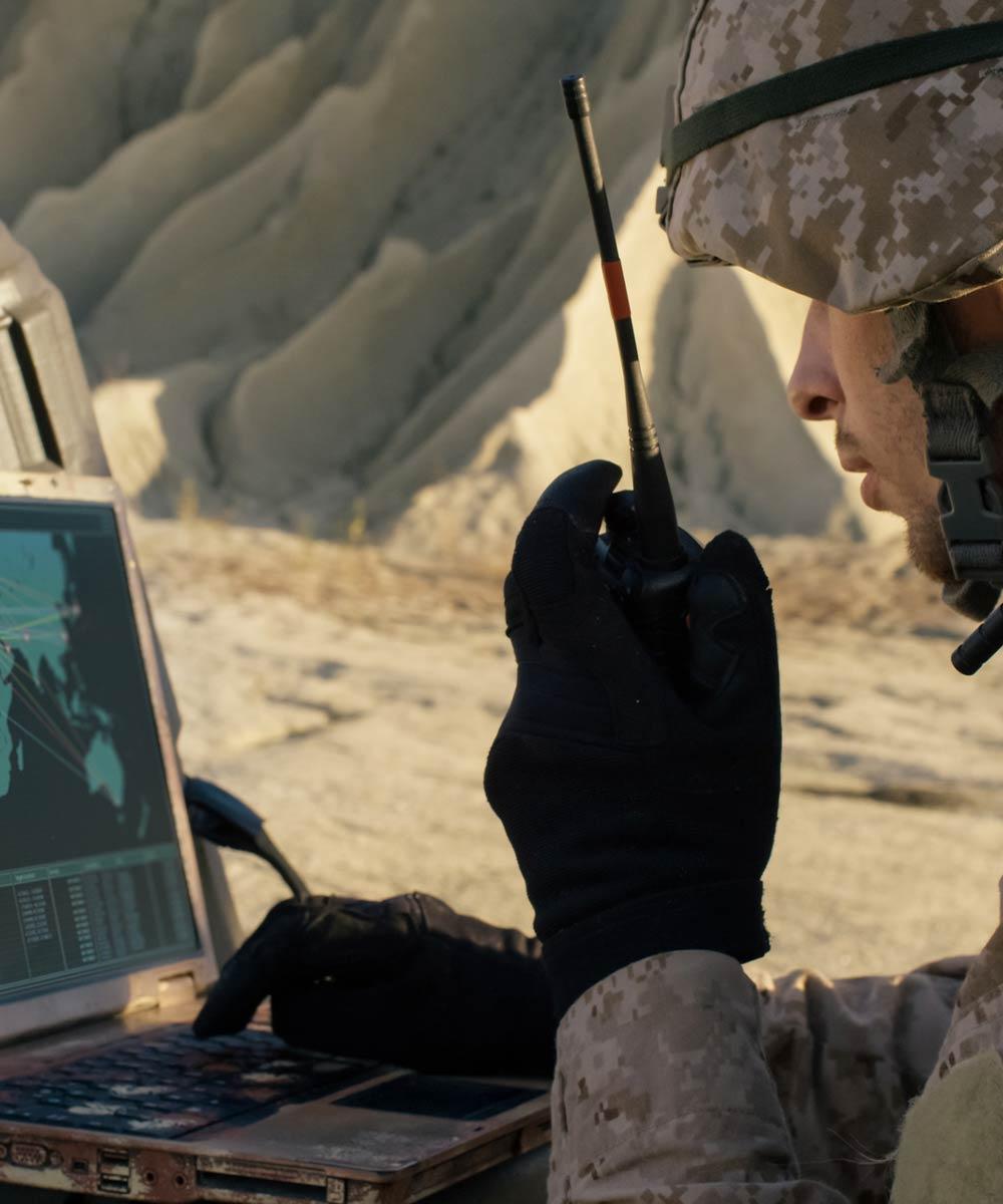 man on walkie talkie looking at computer screen