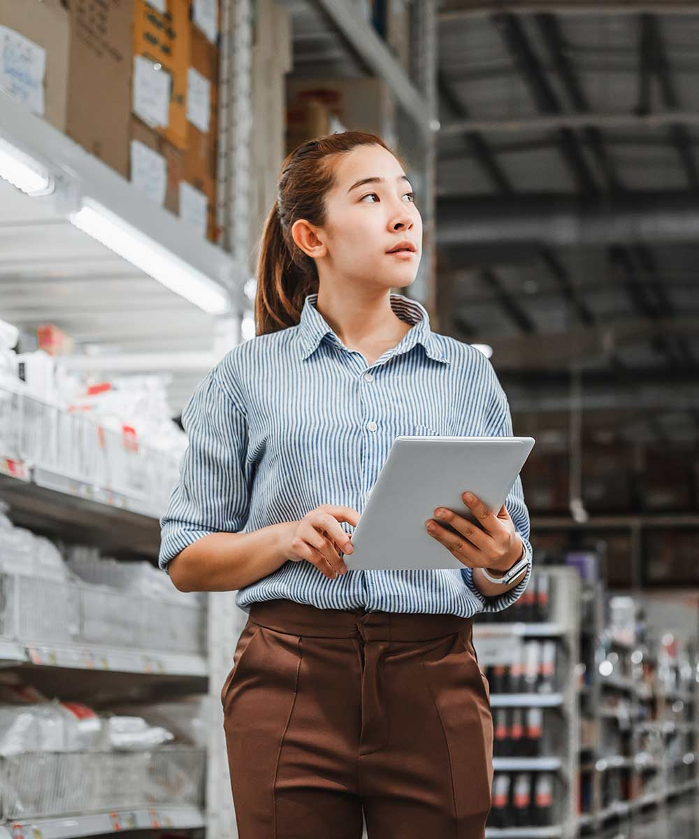 woman holding tablet looking at racks in warehouse